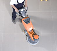 Janitor high speed polishes a commercial floor